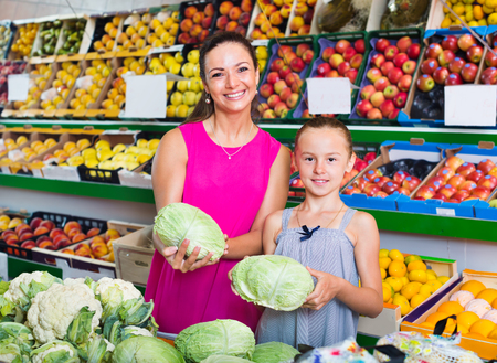 Portrait of smiling mother with girl picking fresh cole at a food store. Focus on both persons Stock Photo