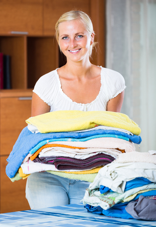 doing chores: Portrait of blonde housewife with stack of washed linen in domestic  interior