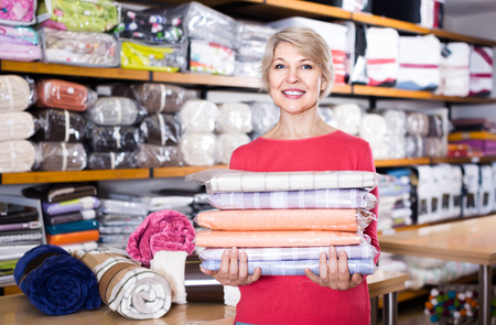 boasting: happy russian  aged woman enjoying purchased home textiles in textile shop Stock Photo