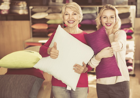 boastful: Happy  positive girl and mature woman customers showing bought pillows in home textile shop Stock Photo