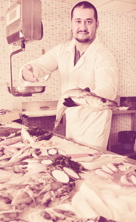 Friendly cheerful man in glove behind counter shows fish in his hand