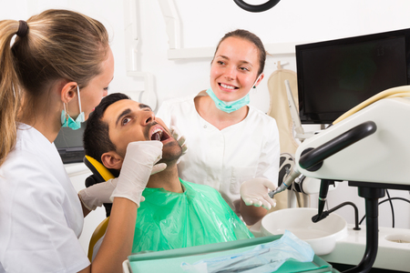 dentist drill: Female dentist with assistant diagnostics the oral cavity of patient at clinic