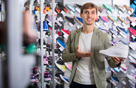 Happy positive man promoting a sporty shoes in the shop Stock Photo