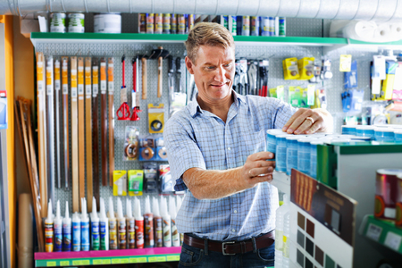 housewares: Portrait of cheerful   smiling male customer selecting paint can in housewares department