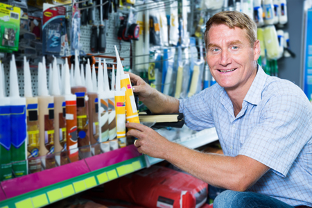 friendly man customer choosing sealant tube in housewares hypermarket
