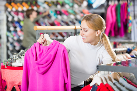 25 35: Smiling girl selecting a warm jacket at the sport boutique