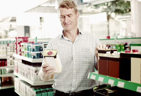 housewares: portrait of mature man holding tin with furniture oil in housewares hypermarket Stock Photo