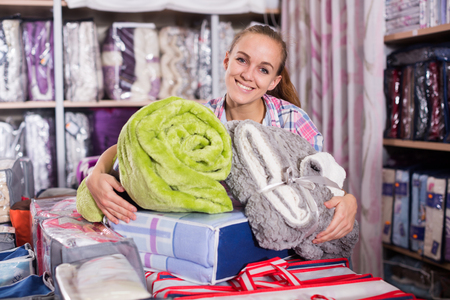 boasting: Young woman enjoying her new blanket and coverlet in textile shop