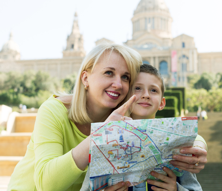 Positive mother and son consulting map guide during sightseeing tour