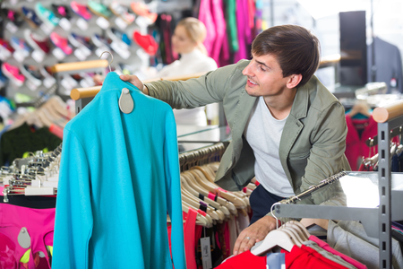 25 35: Positive smiling young man picking a cardigan in the sport shop Stock Photo