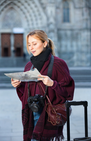 Blond positive girl holding a map in hands and looking for her way Stock Photo