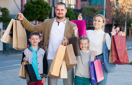 Family with two kids smiling and holding shopping bags in the town