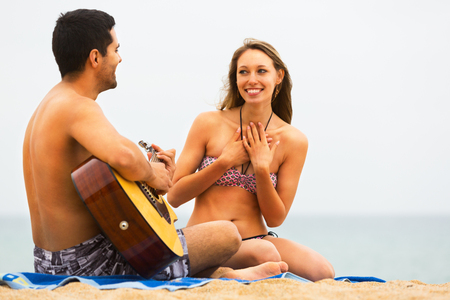 Young couple sitting on the sandy beach with a guitar Stock Photo