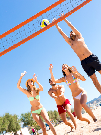 Happy smiling adults playing with a ball on a beach. Man jumping to catch a volley ball