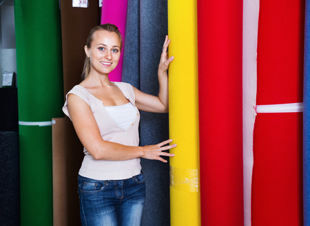 rug texture: Cheerful smiling pleasant woman customer shopping carpet flooring in interior store Stock Photo