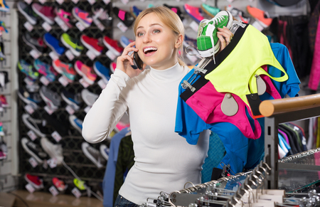 25 35: Positive girl gladly speaking on the phone and choosing a sport bra Stock Photo