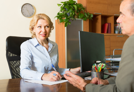 census: Elderly man talking with mature female bank manager about opening saving account