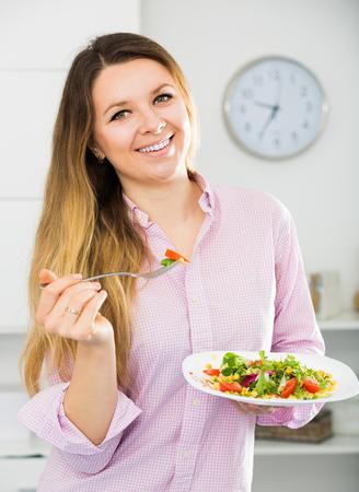 Cheerfull young woman eating tasty green salad at home Stock Photo