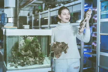 aquarian: Female teenager is holding large yellow-brown sandstone for aquarium decoration in aquarium shop.