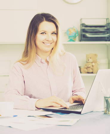 expertize: Positive woman worker working effectively on project in office Stock Photo