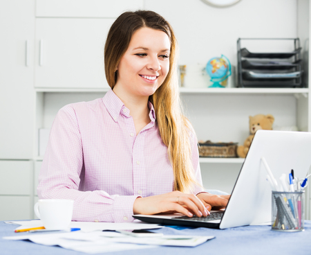 expertize: Young positive female worker working productively on project in office interior Stock Photo