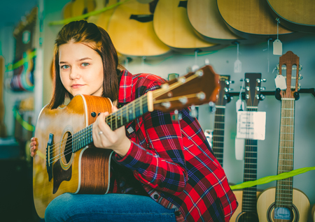 Teen girl examining various acoustic guitars in guitar shop