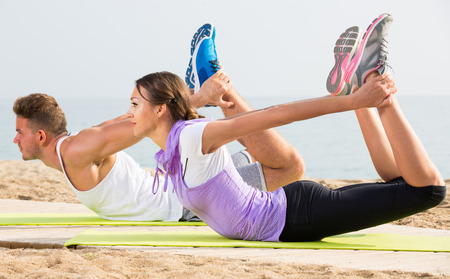 Ordinary man and woman training on beach by sea on sunny morning