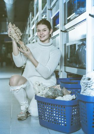 aquarian: Smiling girl in aquarium shop is selecting brown petrified wood for aquarium decoration.