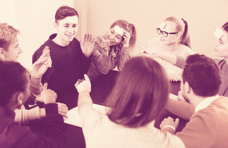 animation teenagers: happy spanish classmates having round of guess-who game during class Stock Photo