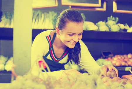 Smiling woman seller putting kiwis on display in grocery shop Stock Photo
