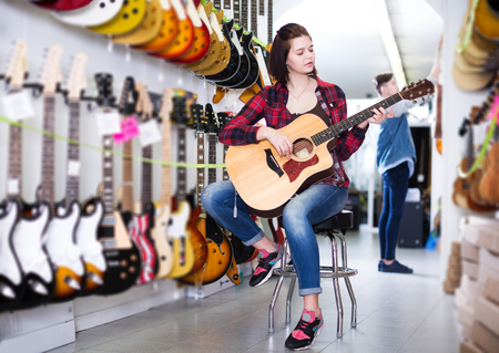 Talented young teenage boy and girl choosing best acoustic guitar in guitar shop Stock Photo