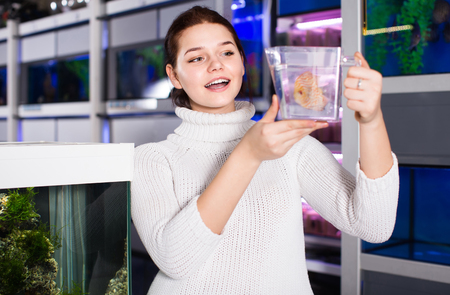 teeny: happy russian girl holding plastic container with big colorful fish breed Discus in aquarium shop Stock Photo