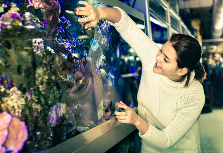 Happy girl in aquarium shop with interest looking at colorful fishes and coral in large aquarium