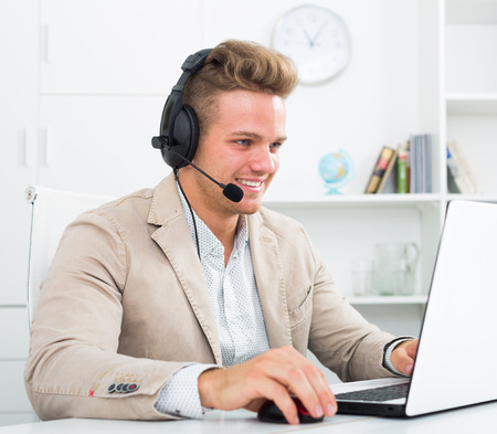Positive call center male operator talking with client in agency
