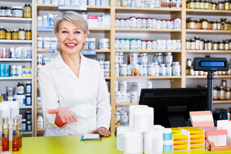 specialized job: Pretty  woman seller showing assortment of care products in specialized shop