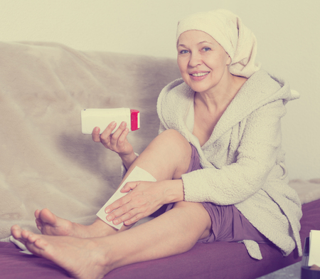 habitual: Elderly woman performing body hair removal at home