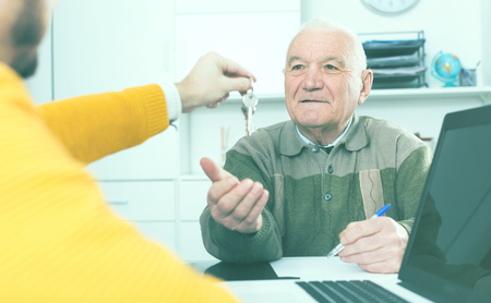 Pensioner and lease agent sign lease contract of apartment at office and hand over keys
