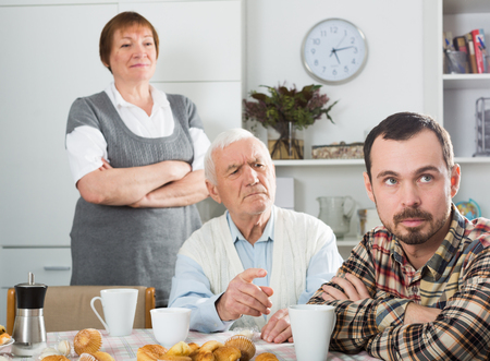 75s: Elderly grandfather teaches his grandson in presence of grandmother Stock Photo