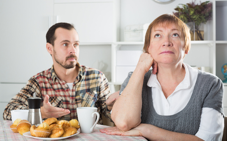 Mature mother was angry at her son and offended him at home