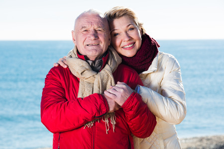 Aged husband and wife taking stroll on beach in cold season