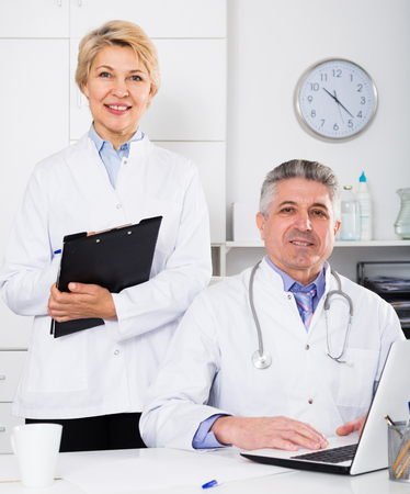 Mature doctor and nurse in white medical gown waiting for patients visit Stock Photo