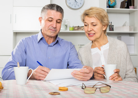 vise: friendly mature couple at table attentively study documents and sign agreement