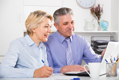 Mature man and woman working together with documents at computer in office