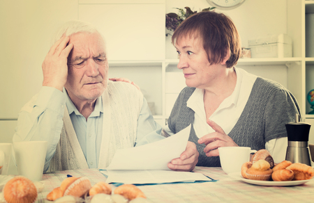 autograph: Elderly husband and wife carefully study contract before signing at home Stock Photo