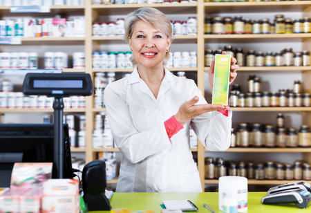 Smiling woman recommending skin care products in specialized shop Stock Photo