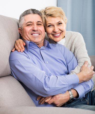 couple on couch: Mature happy european  married couple understand and love each other and are happy in house