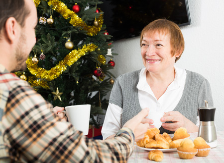 met: Elderly mother and her son drinking coffee and talking at festive Christmas table