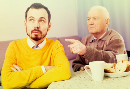 disagreeing: Mature father having disagreement with adult son at home
