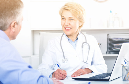 Doctor listens to mature patient and fills information card