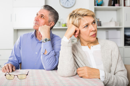 Man and woman 50-54 years old are offended at each other because of the misunderstanding in his home. Stock Photo